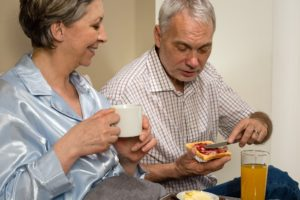 Elderly woman being served breakfast in bed by her husband