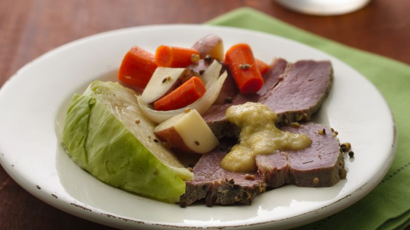 Plate of corned beef, cabbage, carrots, potatoes, onions and stone ground mustard