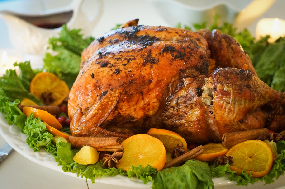 Cooked turkey on a platter with lettuce, orange slices, and spices