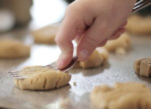 child pressing fork into cookie dough