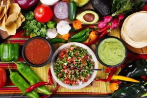 fresh salsa in a bowl with the individual ingredients surrounding the bowl.