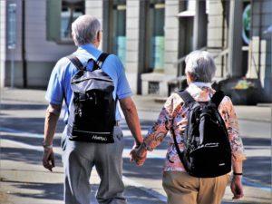 senior couple walking with backs packs