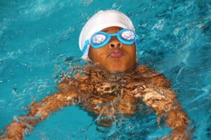 Young boy in pool with goggles on