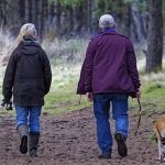 woman and man walking a dog