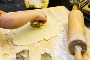 child cutting rolled cookies