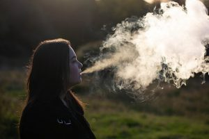 female exhaling a large vape cloud