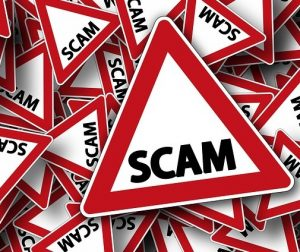 Triangle warning sign with word SCAM