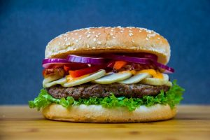 Burger with lettucs, pickles, onions on a sesame bun