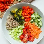 bowl with whole grain, broccoli, red peppers, cucumbers, carrots, tomatoes and celery