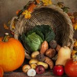 pumpkin and fall vegetables in front of a fall leaf decorated basket