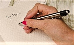 womens hand writing in a planner