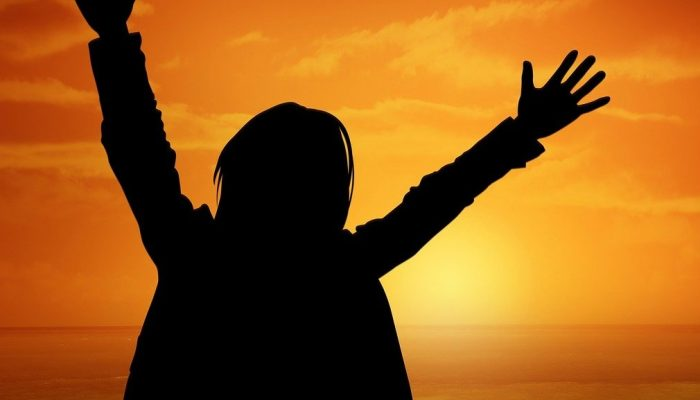 Silhouette of person with both hands in the air in front of a sunset