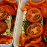 Two casserole dishes filled with red bell peppers, tomatoes, cheese and herbs