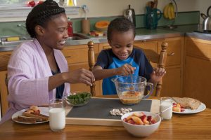 Mom and boy preparing breakfast in small portions