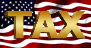 the word tax In front of an American flag