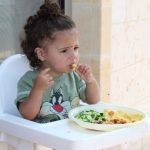 child in highchair, eating