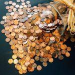 coins spilling out of jar on side