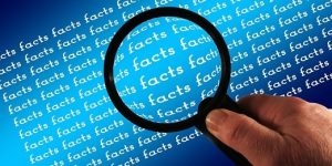 the word facts and a magnifying glass